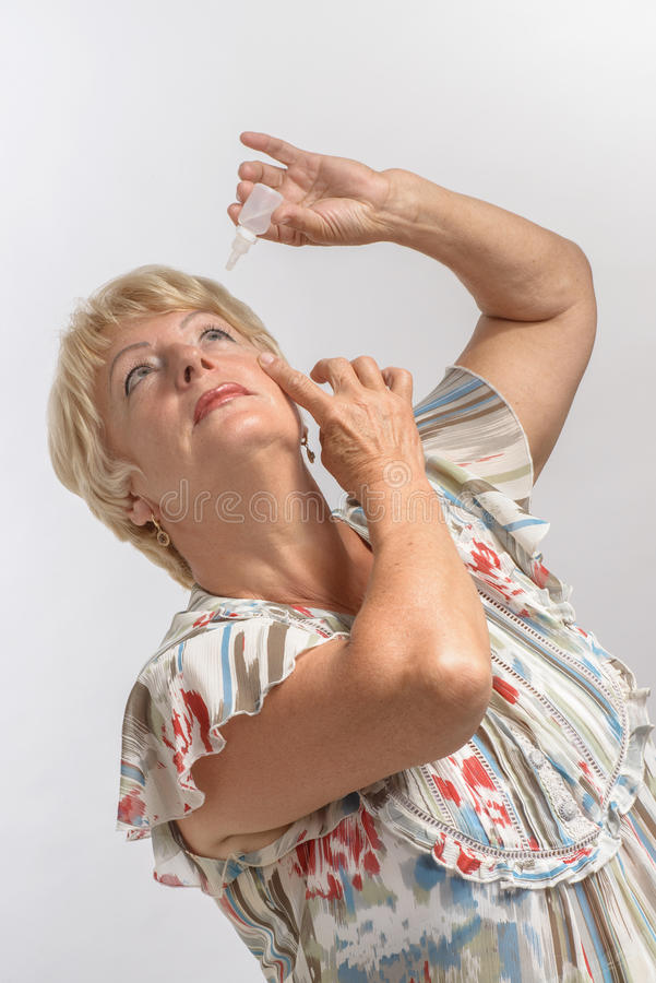 Elderly woman treats her eyes with medication royalty free stock photo
