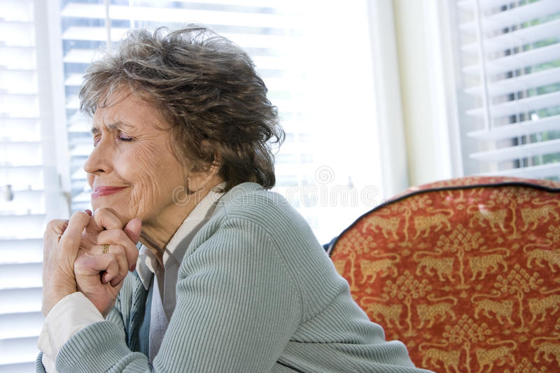 Elderly woman upset sitting alone by window. With eyes shut royalty free stock photography