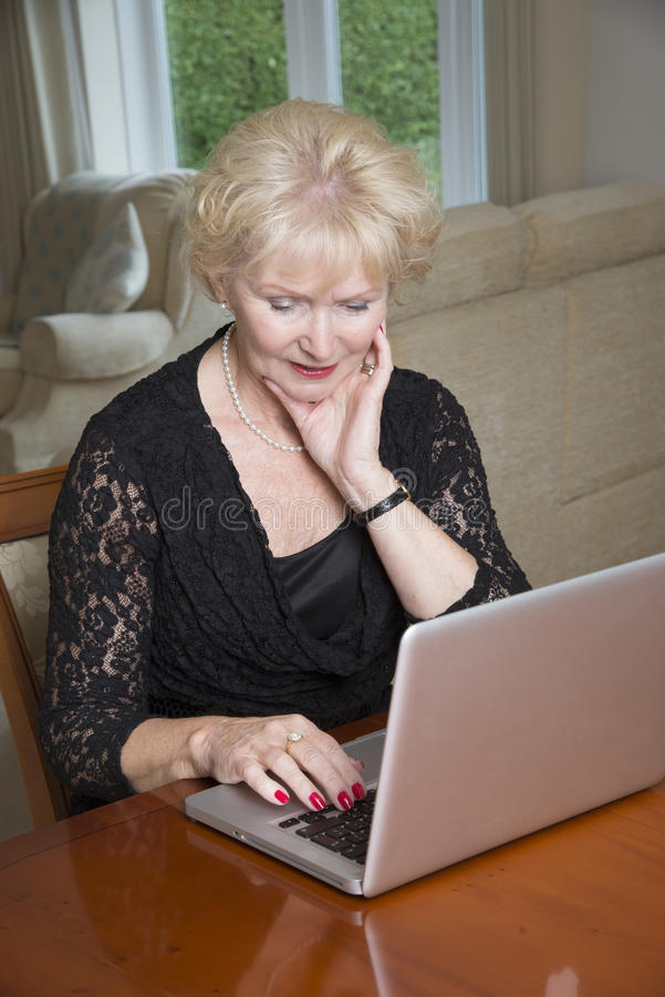 Elderly woman using laptop computer royalty free stock photo