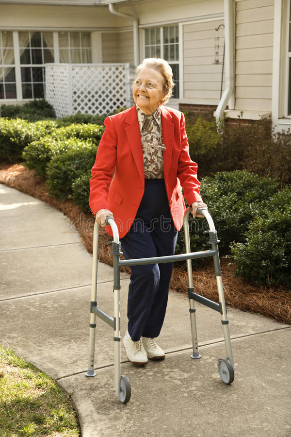 Elderly Woman Using Walker. Smiling elderly woman takes a stroll outdoors with her walker. Vertical shot stock images