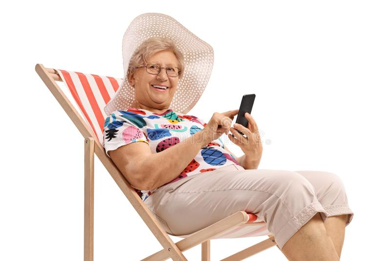 Elderly woman on a vacation with a phone sitting in a deck chair and looking at the camera. Isolated on white background royalty free stock photography