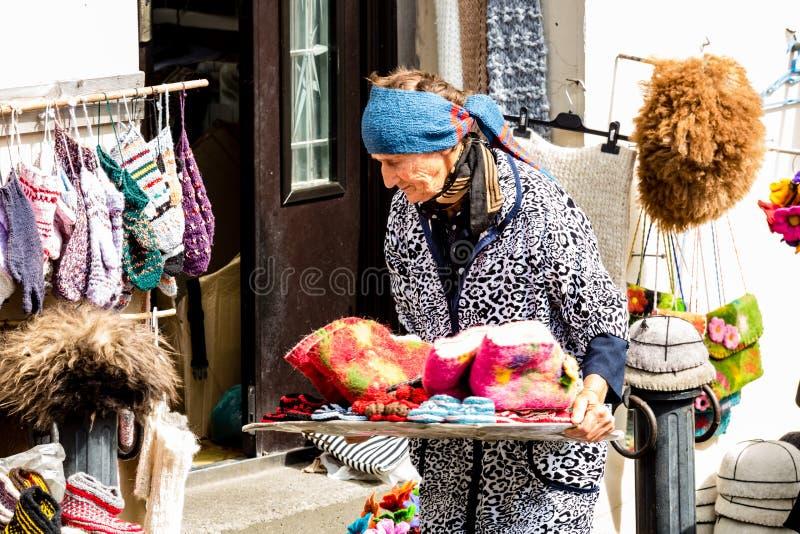 Elderly woman vendor selling socks, woolen slippers and bright souvenirs on the street of Signagi town, Kakheti region, Georgia royalty free stock images