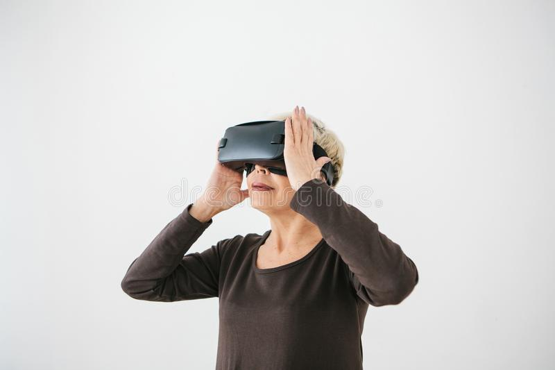 An elderly woman in virtual reality glasses. An elderly person using modern technology. stock photography