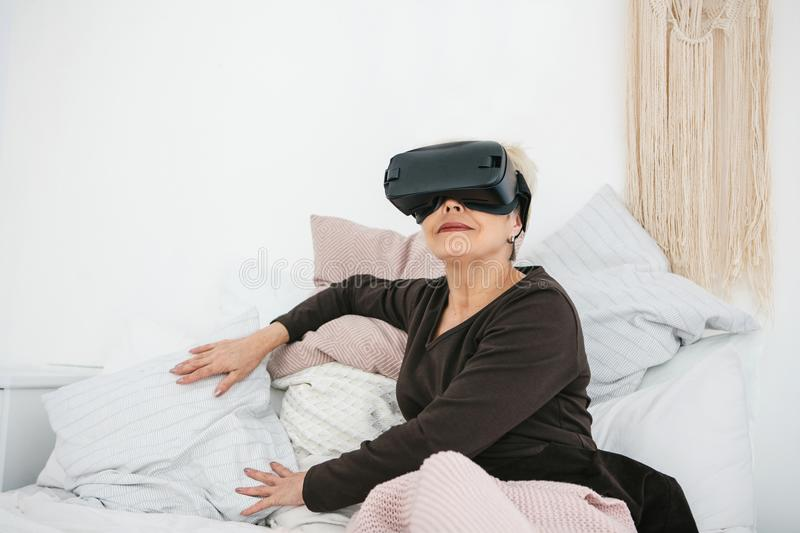 An elderly woman in virtual reality glasses. An elderly person using modern technology. An elderly woman in virtual reality glasses. An elderly person using stock image