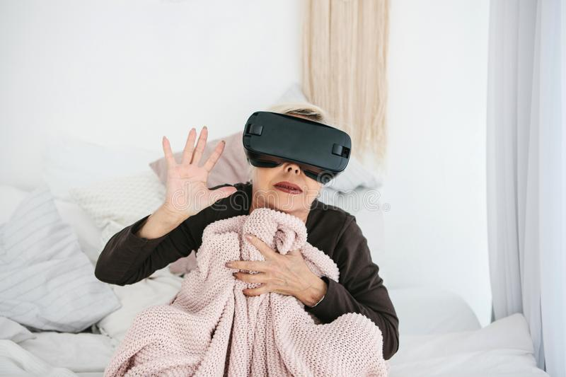 An elderly woman in virtual reality glasses. An elderly person using modern technology. An elderly woman in virtual reality glasses. An elderly person using stock photography
