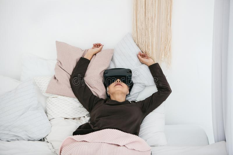 An elderly woman in virtual reality glasses. An elderly person using modern technology. An elderly woman in virtual reality glasses. An elderly person using stock images