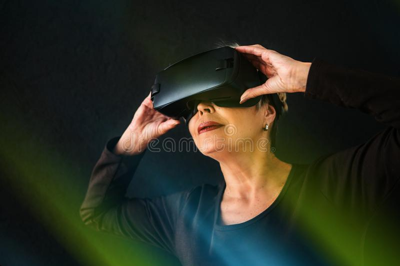 An elderly woman in virtual reality glasses. An elderly person using modern technology. An elderly woman in virtual reality glasses. An elderly person using royalty free stock image