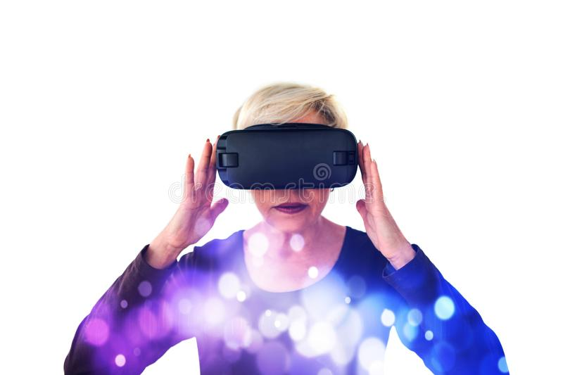 An elderly woman in virtual reality glasses. An elderly person using modern technology. An elderly woman in virtual reality glasses. An elderly person using stock photo