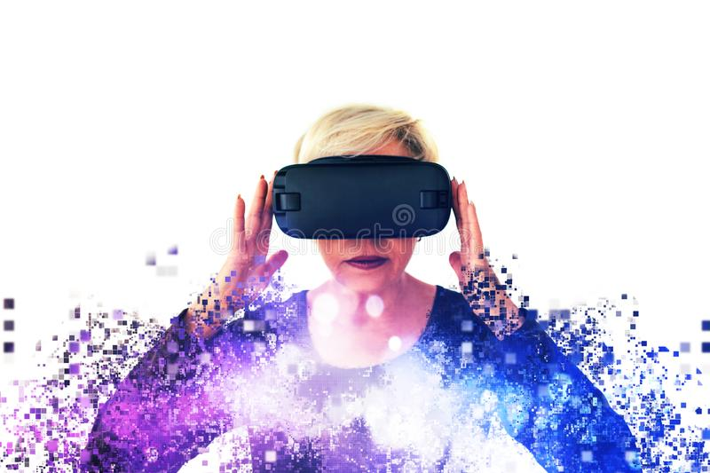 An elderly woman in virtual reality glasses is scattered by pixels. Conceptual photography with visual effects with an. Elderly person using modern technology royalty free stock photos