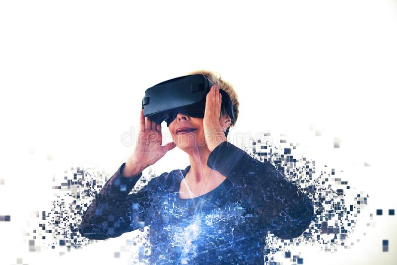 An elderly woman in virtual reality glasses is scattered by pixels. Conceptual photography with visual effects with an. Elderly person using modern technology stock image