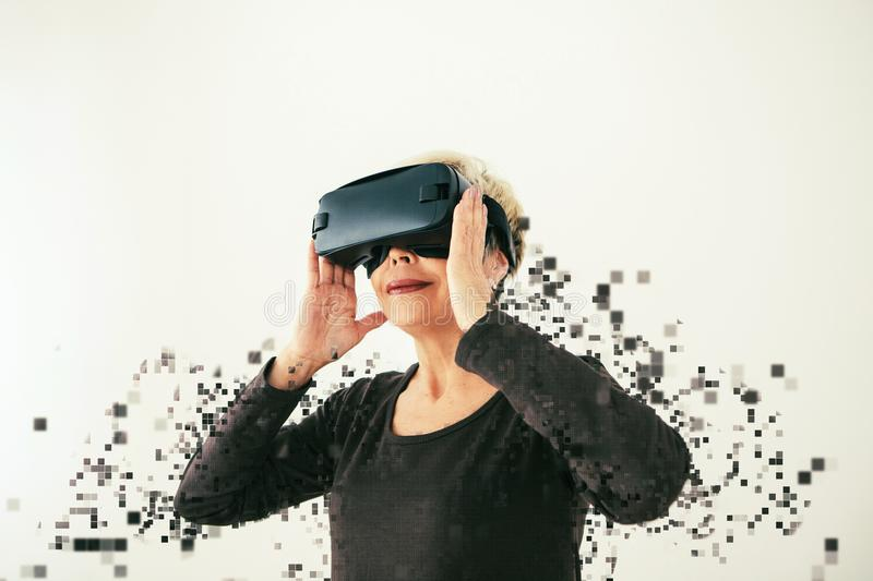 An elderly woman in virtual reality glasses is scattered by pixels. Conceptual photography with visual effects with an. Elderly person using modern technology royalty free stock photo
