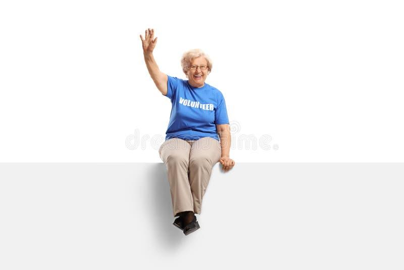Elderly woman volunteer sitting on a white panel and waving. Full length shot of an elderly woman volunteer sitting on a white panel and waving isolated on white stock image