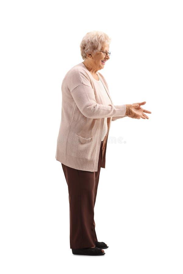 Elderly woman waiting to receive something. Full length shot of an elderly woman waiting to receive something isolated on white background stock photography