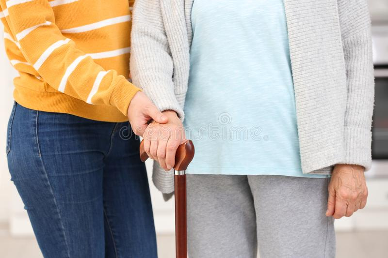 Elderly woman with walking cane and female caregiver. Closeup view royalty free stock photos