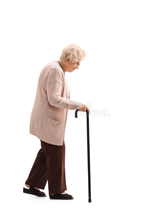 Elderly woman with a walking cane. Full length profile shot of an elderly woman with a walking cane isolated on white background stock images
