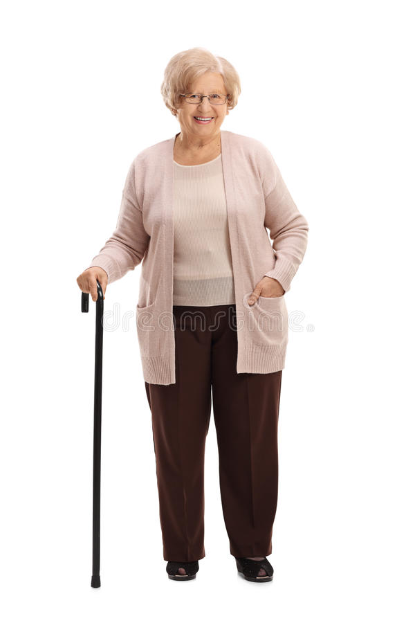 Elderly woman with a walking cane smiling. Full length portrait of an elderly woman with a walking cane smiling isolated on white background royalty free stock image