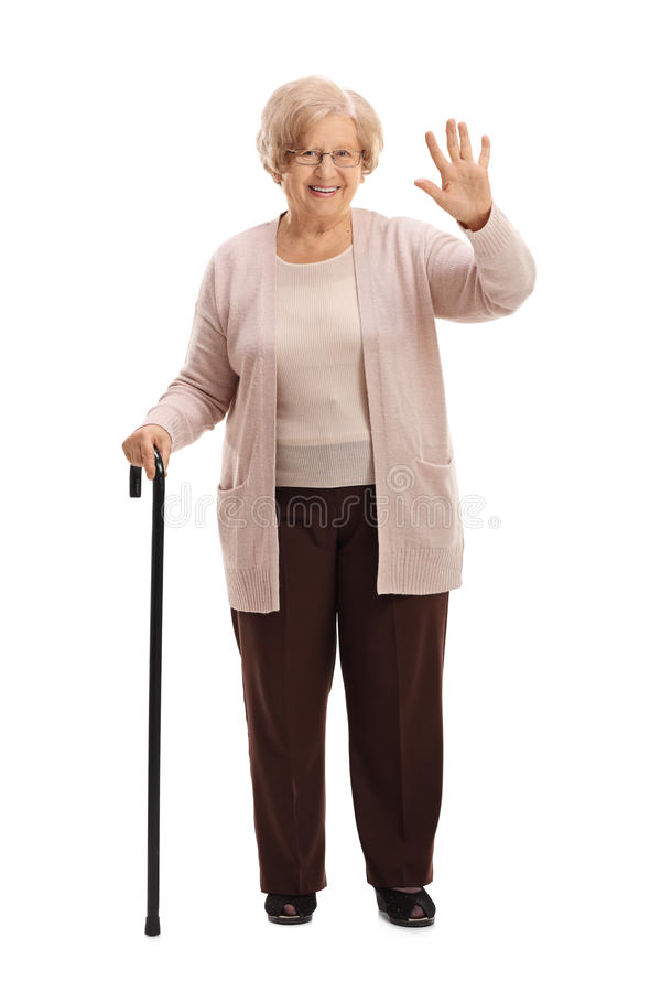 Elderly woman with a walking cane waving. Full length portrait of an elderly woman with a walking cane waving isolated on white background stock image