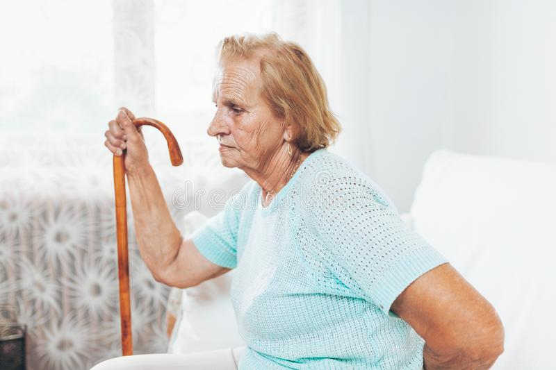 Elderly woman with a walking stick royalty free stock images