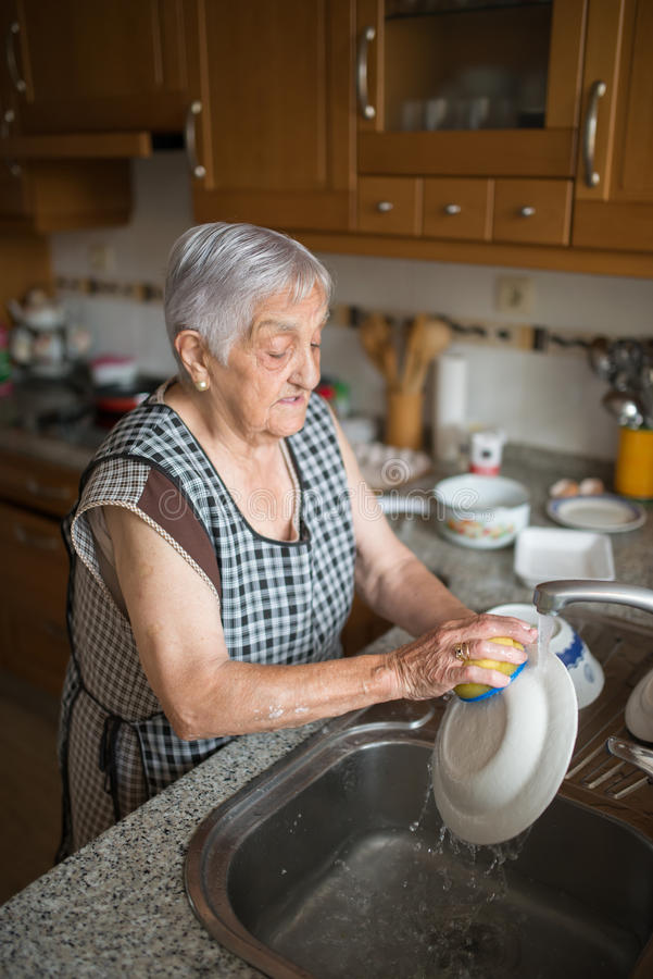 Elderly woman washing dishes stock images