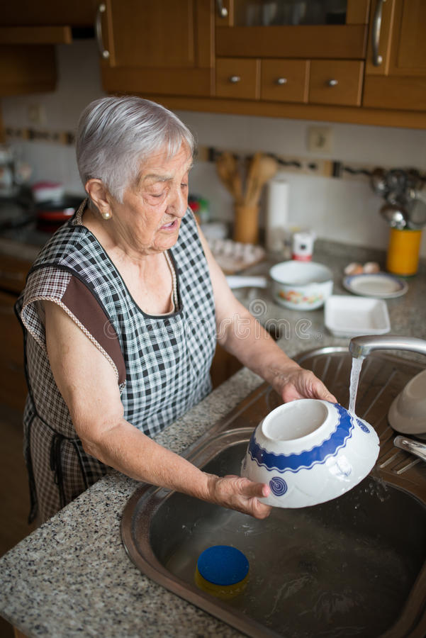 Elderly woman washing dishes royalty free stock image