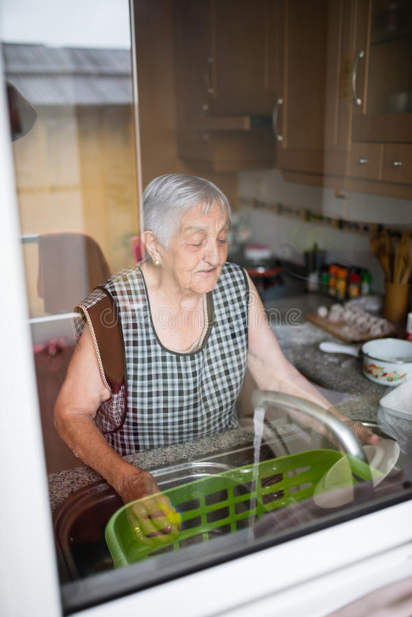 Elderly woman washing dishes royalty free stock images