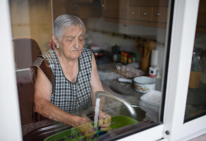 Elderly woman washing dishes stock image
