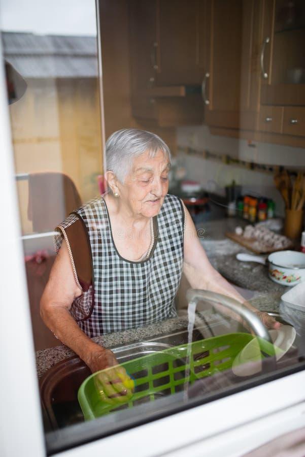 Elderly woman washing dishes royalty free stock photo