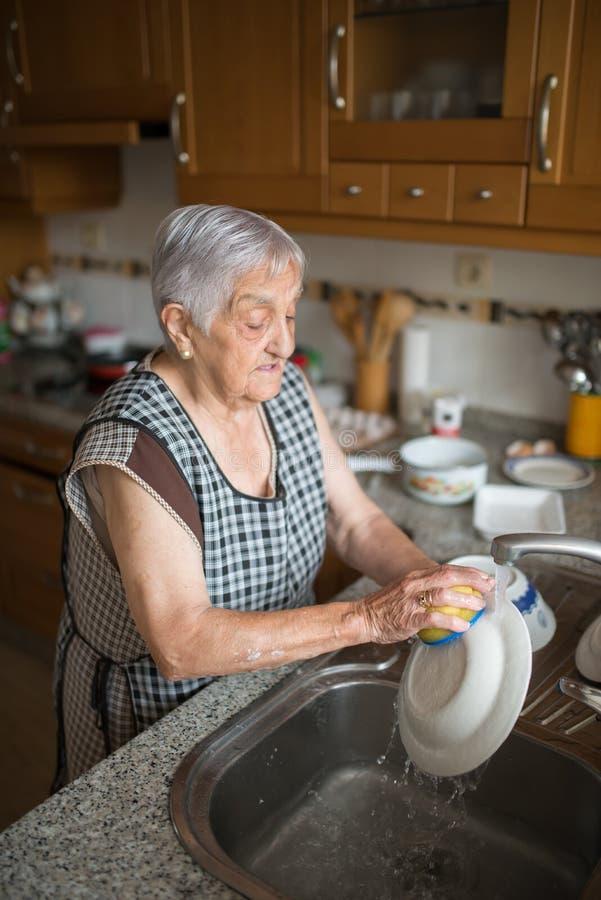 Elderly woman washing dishes stock image