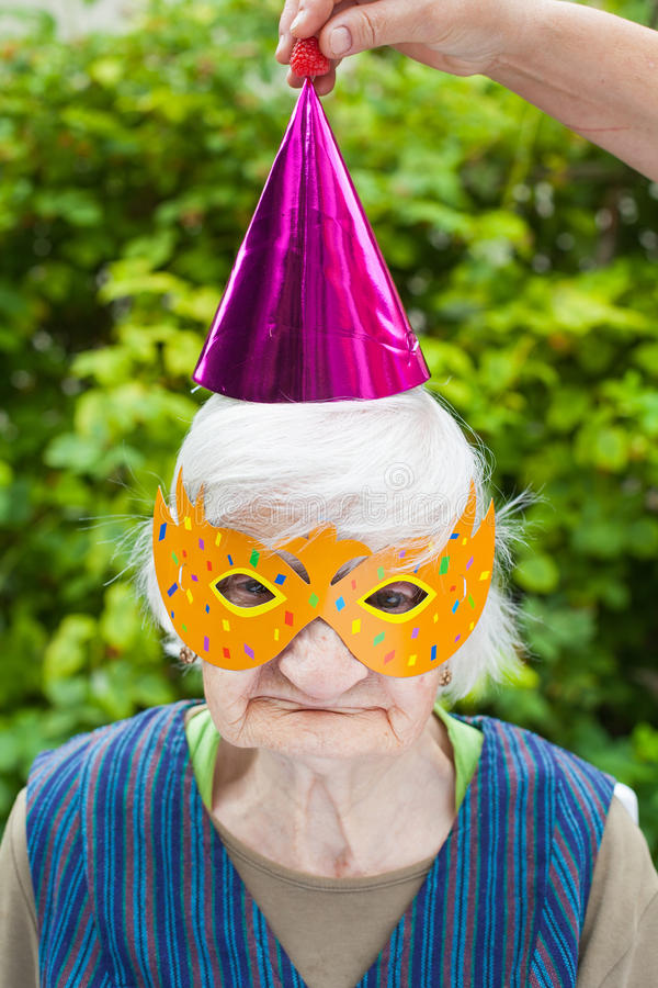 Elderly woman wearing colorful mask & hat celebrating. Portrait of a happy elderly woman celebrating birthday outdoor, wearing a colorful hat and mask stock photos