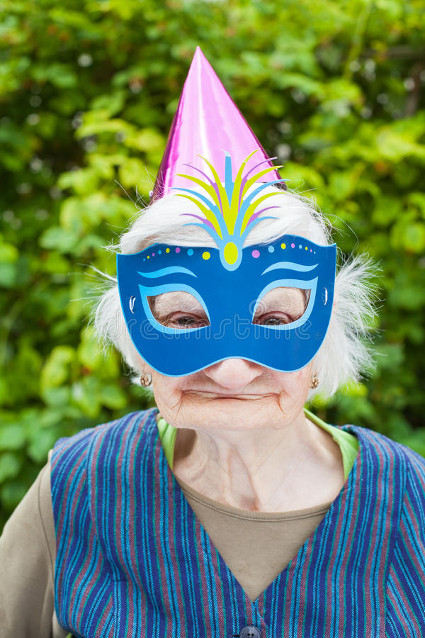 Elderly woman wearing colorful mask & hat celebrating. Portrait of a happy elderly woman celebrating birthday outdoor, wearing a colorful hat and mask stock images