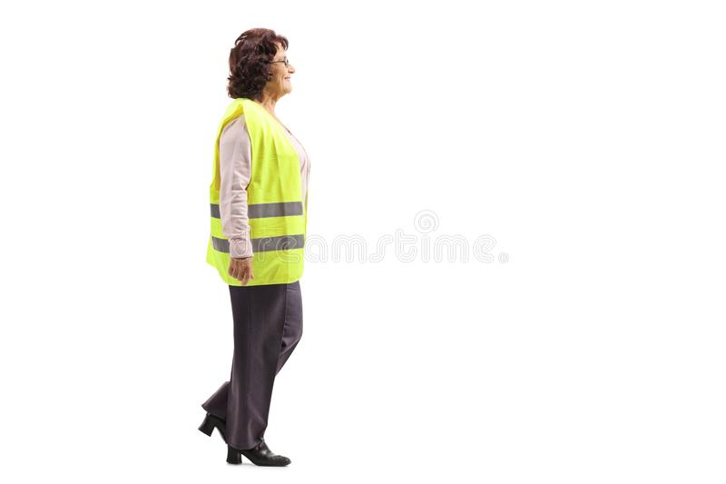 Elderly woman wearing a safety vest walking stock photography
