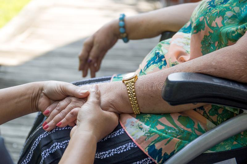 Elderly woman in wheelchair holding hands with caregiver. In the garden royalty free stock photography