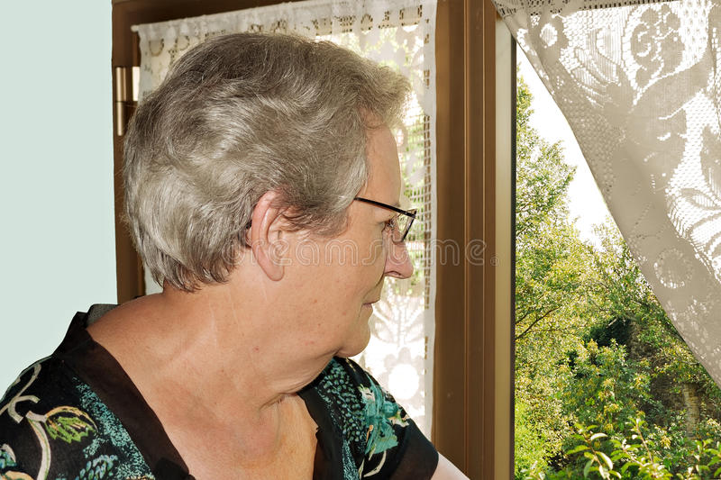 Elderly woman at window stock images