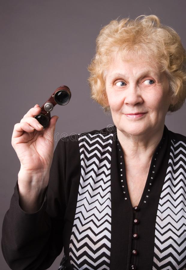 The elderly woman witn binocular. stock photo