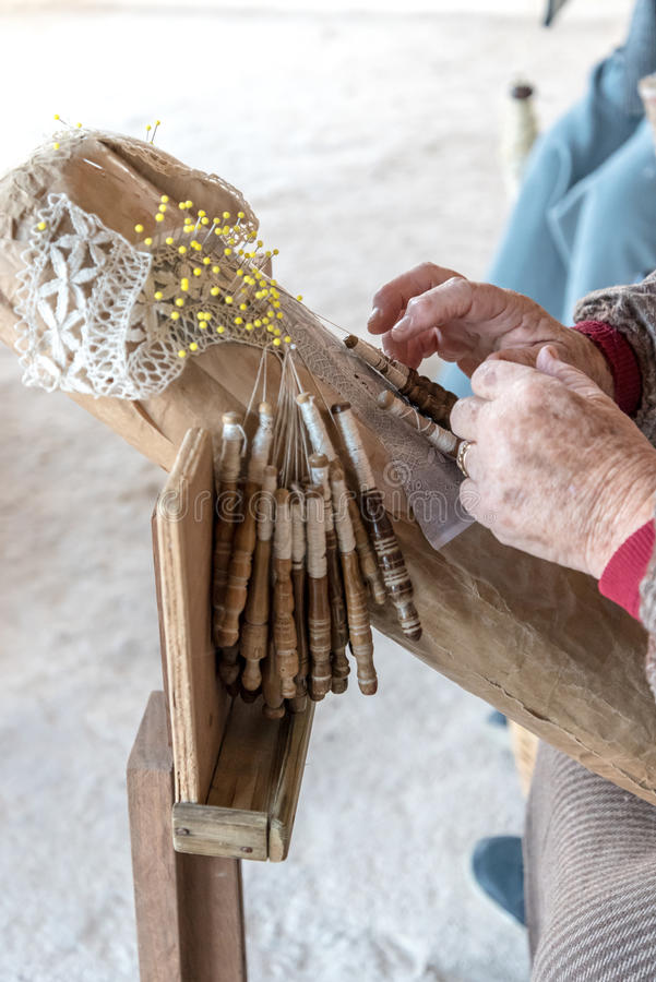 An elderly woman working on hand-made lace or bizzilla stock images