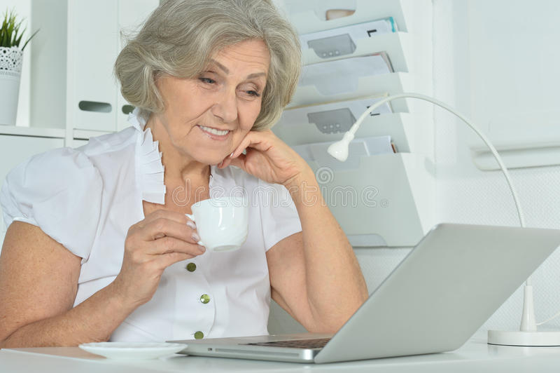 Elderly woman working on laptop. Happy Elderly woman working on laptop in office stock photos