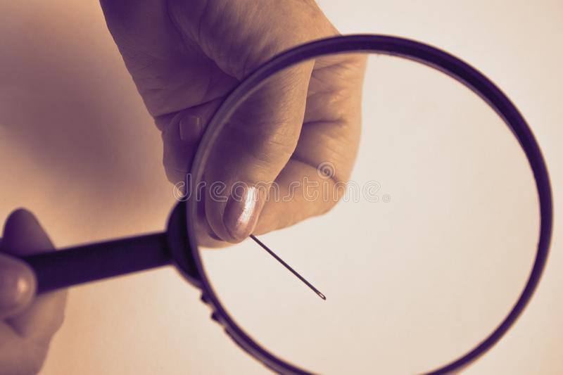 An elderly woman with wrinkled fingers holds a magnifying glass and through the transparent glass is visible a steel royalty free stock photo