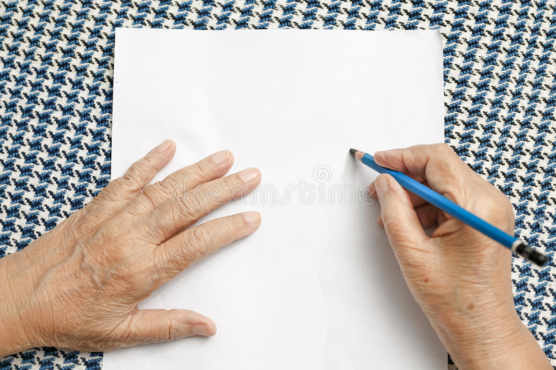 Elderly woman writing on blank paper stock photo