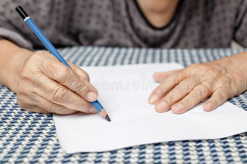Elderly woman writing on blank paper royalty free stock photography