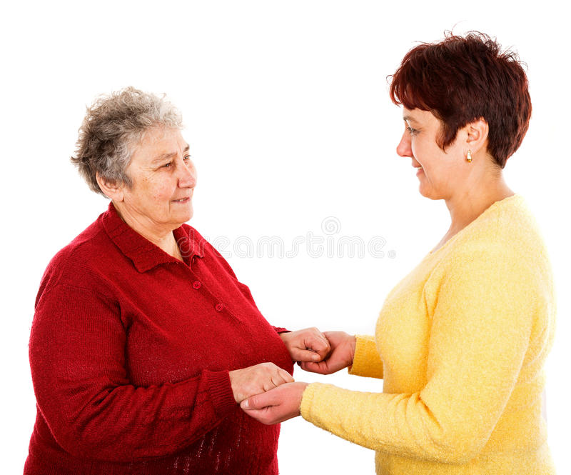 Elderly woman and young caregiver. Photo of young caregiver holding elderly women hands stock image