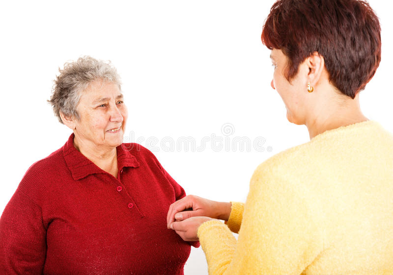 Elderly woman and young caregiver. Photo of young caregiver holding elderly women hands stock images