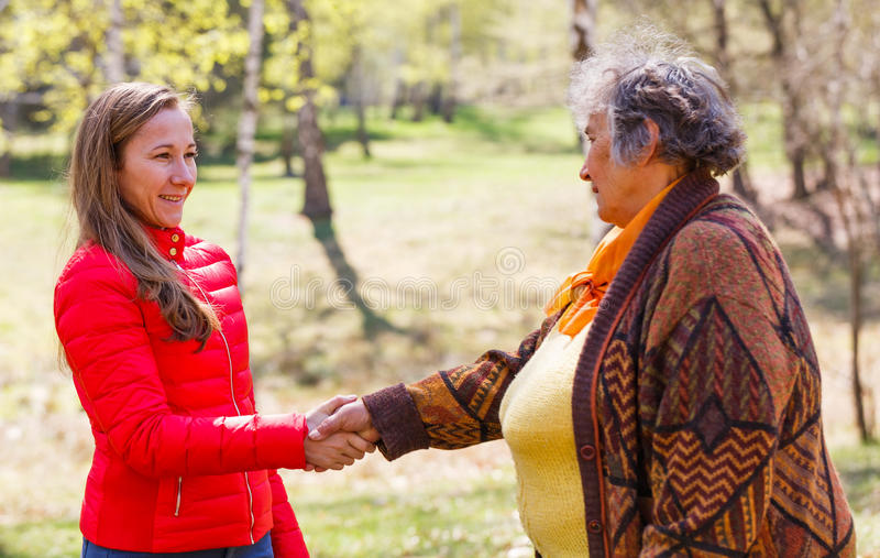 Elderly woman and young caregiver. Elderly women shaking hand with the young caregiver royalty free stock images