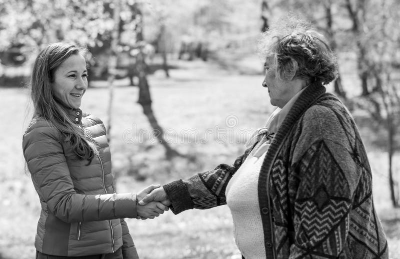 Elderly woman and young caregiver. Elderly women shaking hand with the young caregiver stock images