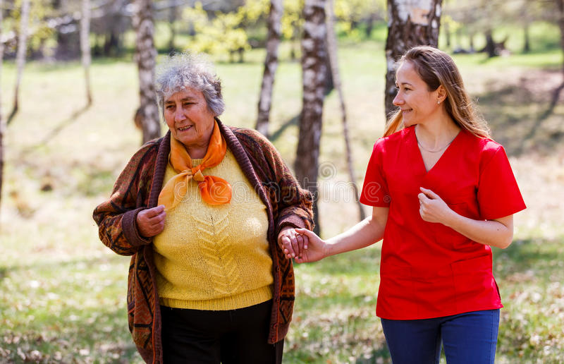 Elderly woman and young caregiver. Elderly women and young caregiver walking in the park royalty free stock image