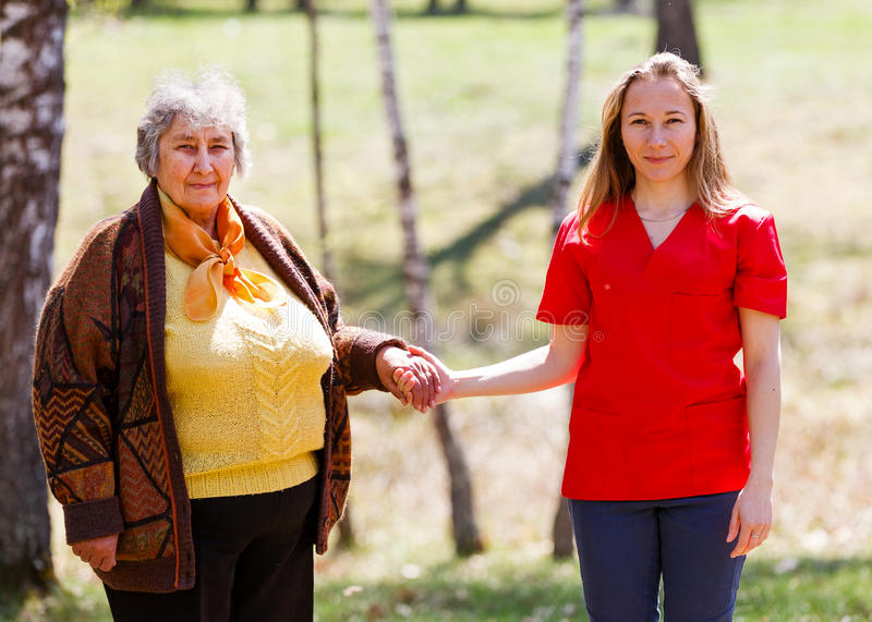 Elderly woman and young caregiver. Elderly women and young caregiver walking in the park royalty free stock photo