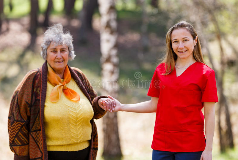 Elderly woman and young caregiver. Elderly women and young caregiver walking in the park stock image