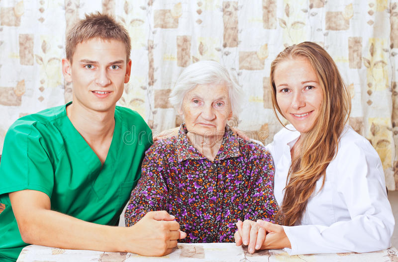 Elderly woman with the young doctor. Elderly women with the two young grandchild royalty free stock photo