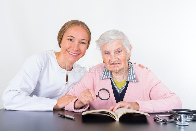 Elderly woman and young doctor. Photo of elderly women with the young doctor stock photography