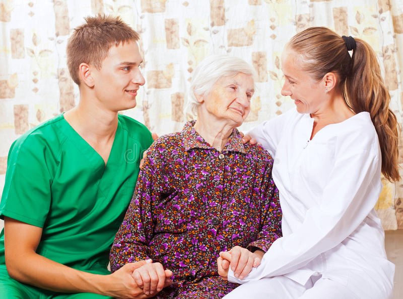 Elderly woman with the young doctors. Elderly women with the sweet young doctors stock photo
