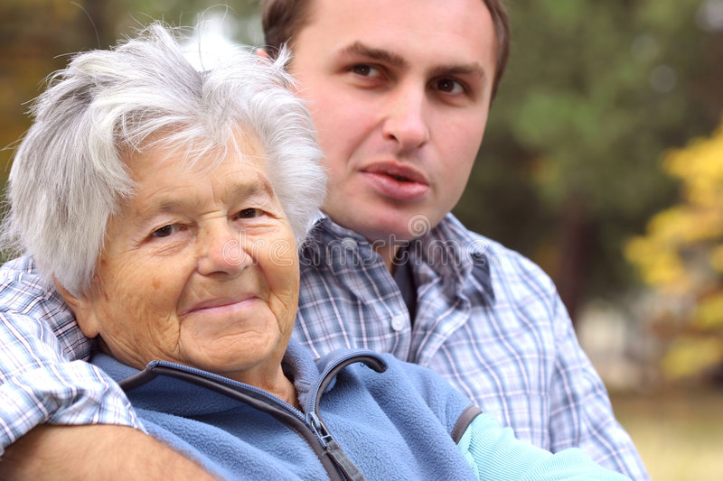 Elderly woman and young man. Sitting on the bench stock photos